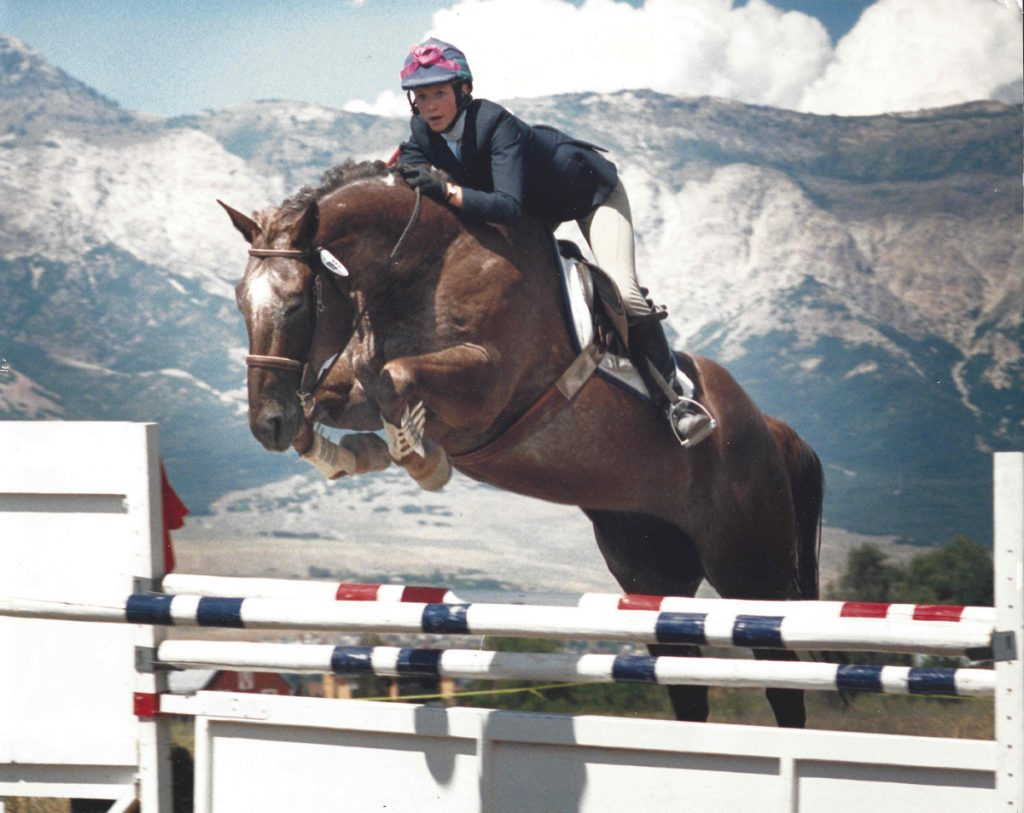 A young woman jumps on her horse during an equestrian competition with mountains in the background.
