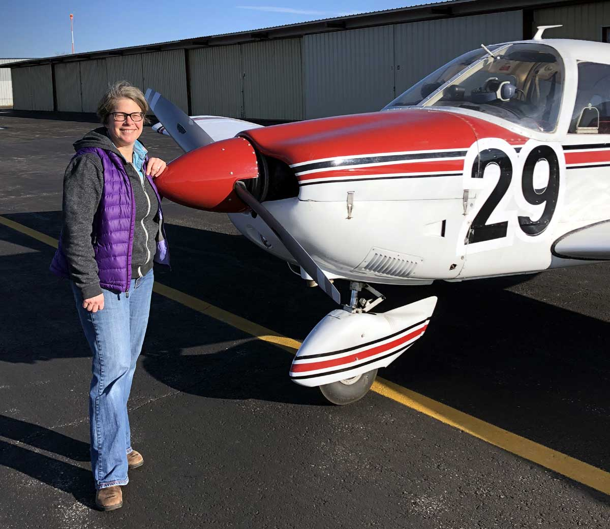 pilot stands at front of small plane