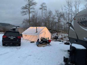 This photo shows a hunting camp with tents and mobile campers.