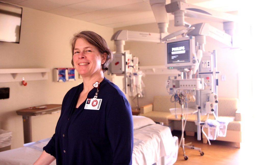 nurse stands in ICU room