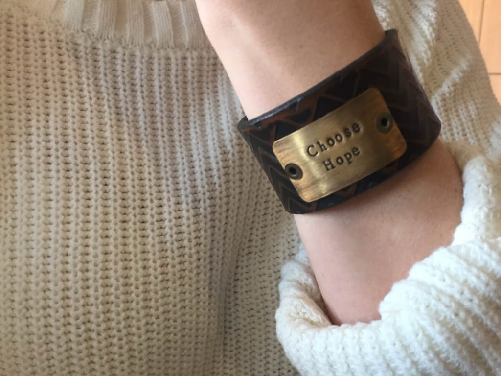 "a woman shows her bracelet that says ""Choose Hope."" It's the mantra for moms who have lost their babies."