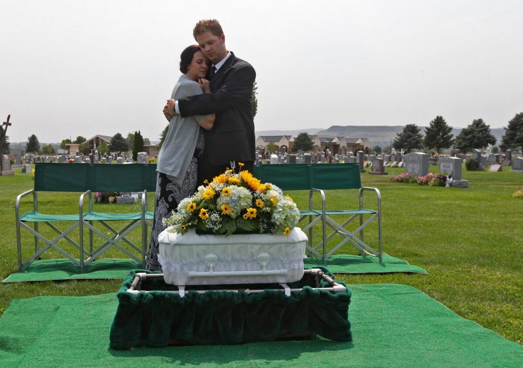 Parents at a funeral for a baby. They hug as a small white casket sits in front of them.