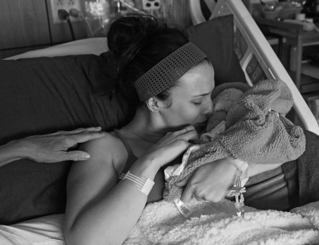 a photo shows a mom kissing her infant son who is wrapped in a blanket. He died from a fatal disease soon after birth.
