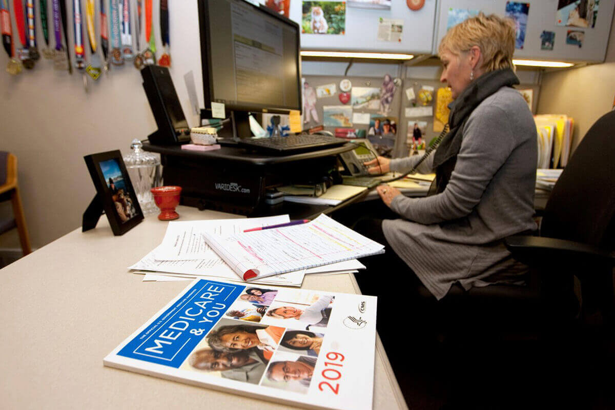 Women talks on the phone at her computer desk with Medicare paperwork laid out.