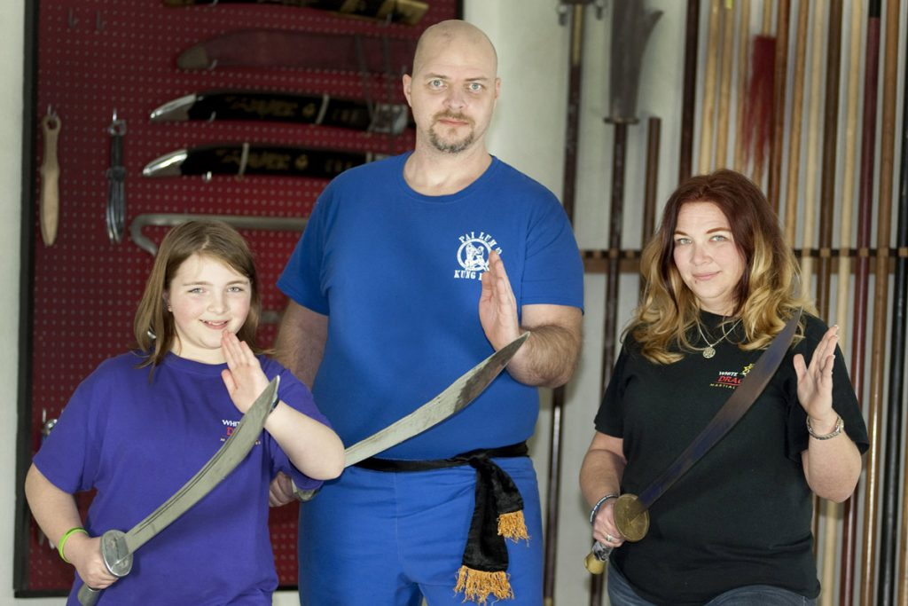 Dan stands with his family at the kung fu place, all holding swords.