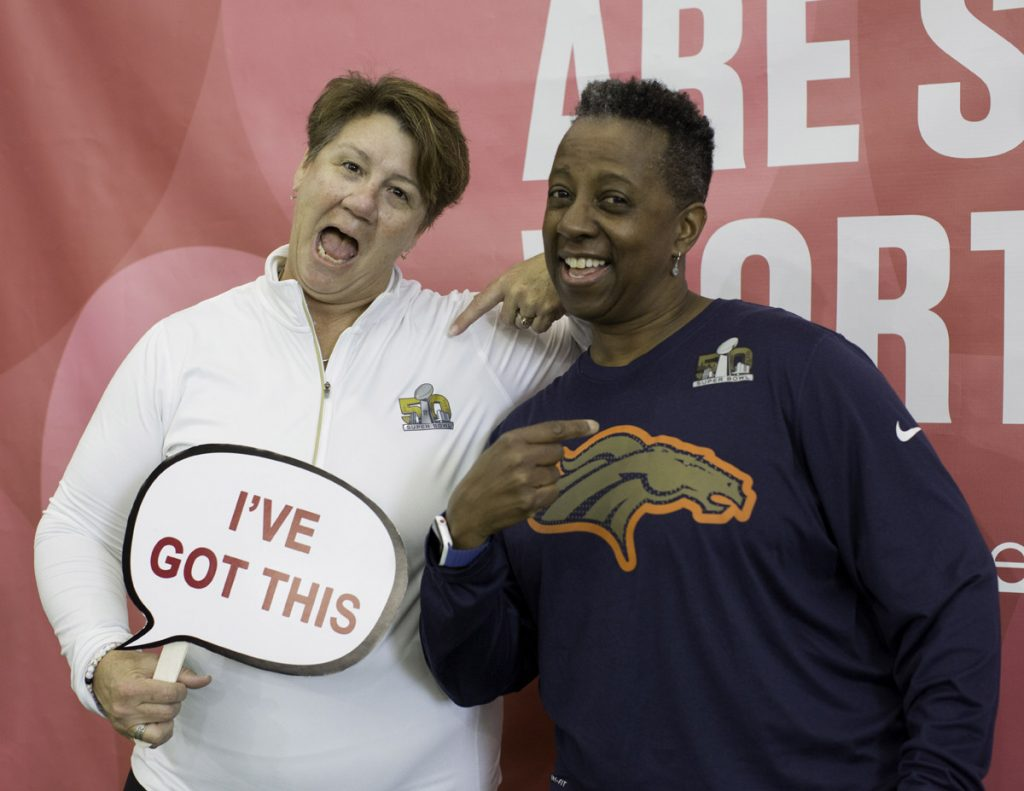"""Two women pose at a photo booth. One is holding a sign that says, """"I've got this."""""""