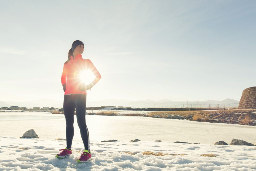 A woman stands oustide on a sunny winter morning.