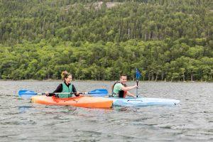 two people kayaking on a mountain lake