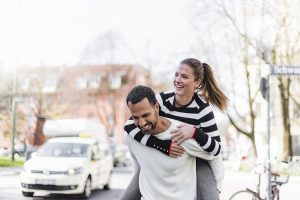 man giving women a piggyback ride on the sidewalk