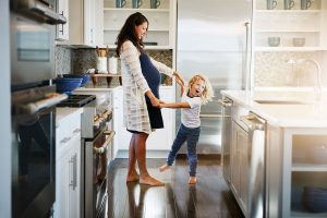 pregnant mom dancing with child in kitchen