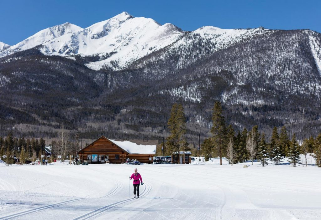 A cross-country skier enjoys the Frisco Nordic Center with a lodge and a peak in the bakcground.