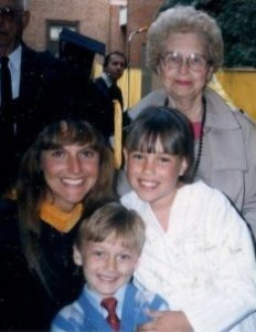 donna with her graduation gown and cap posing with two kids and mother