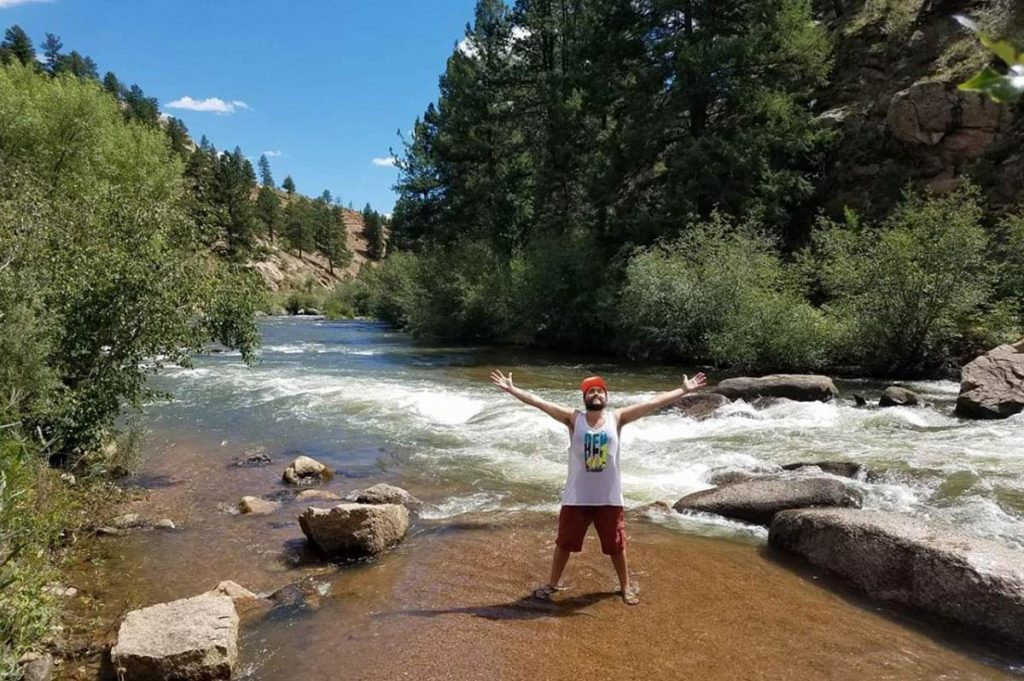 A young man stands in a river with his arms outstretched. He's celebrating life after seizures.