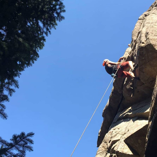 a man is rock climbing outdoors. We see him from below with a big cliff, pine trees and blue sky.