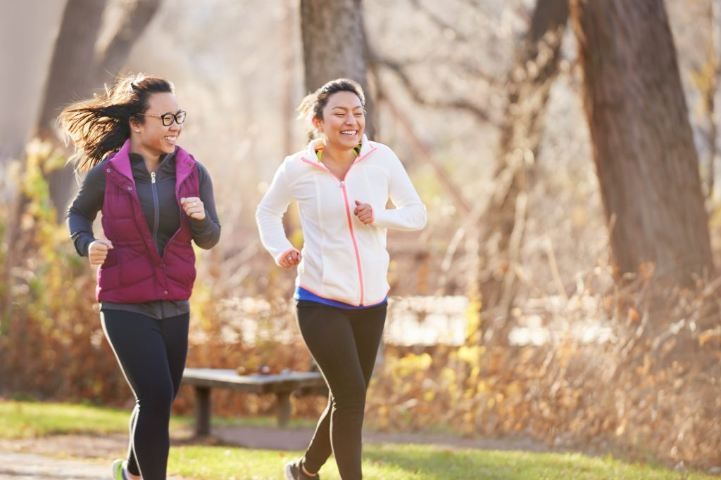 Two women jog in a park