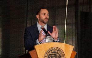 Dr. Armando Vidal speaking at a lectern.