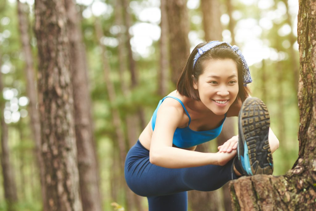 A woman stretches outdoors before an activity.