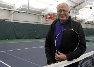 Jim holds a tennis racket on the court of his local tennis club.