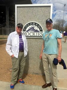 Jim stands next to his brother in front of the Colorado Rockies sign
