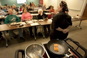 salmon cooks in a skillet while women talks and room of people listen.