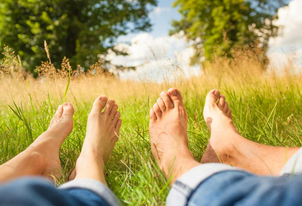 A picture of bare feet in tall grass.