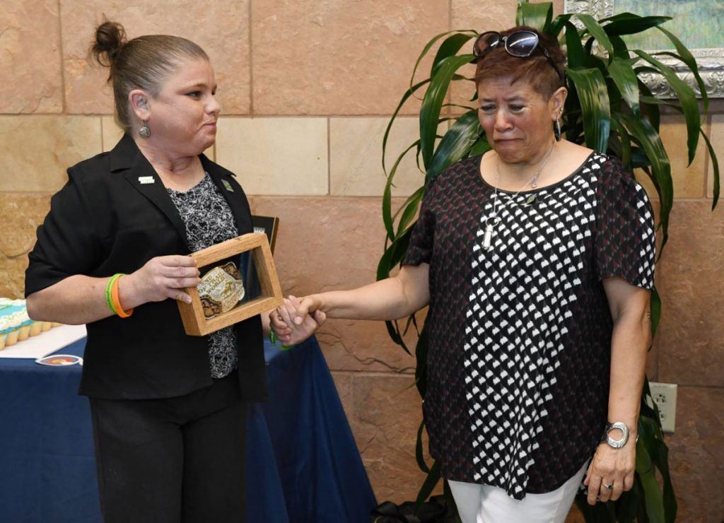 A kidney transplant recipient gives her donor's mother a rodeo belt buckle to honor the kidney donor.