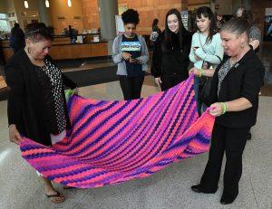 Sara Millard and Ruth Sena admire a blanket that Sena made for Millard. It's purple with orange and blue.