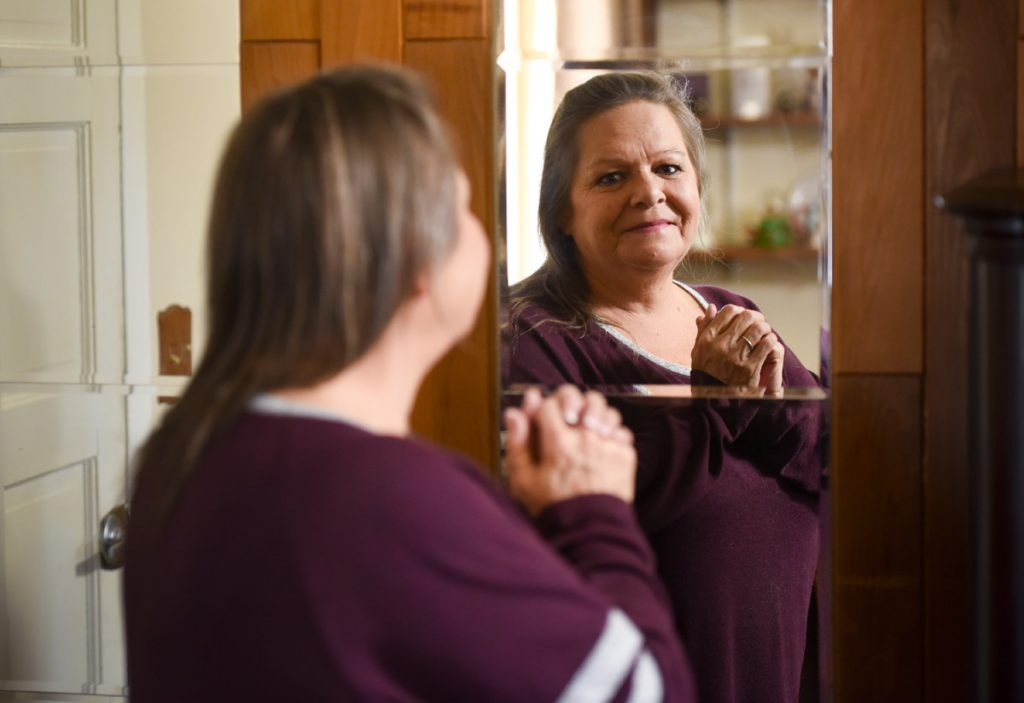 A former blind woman looks into a mirror to see her own face.