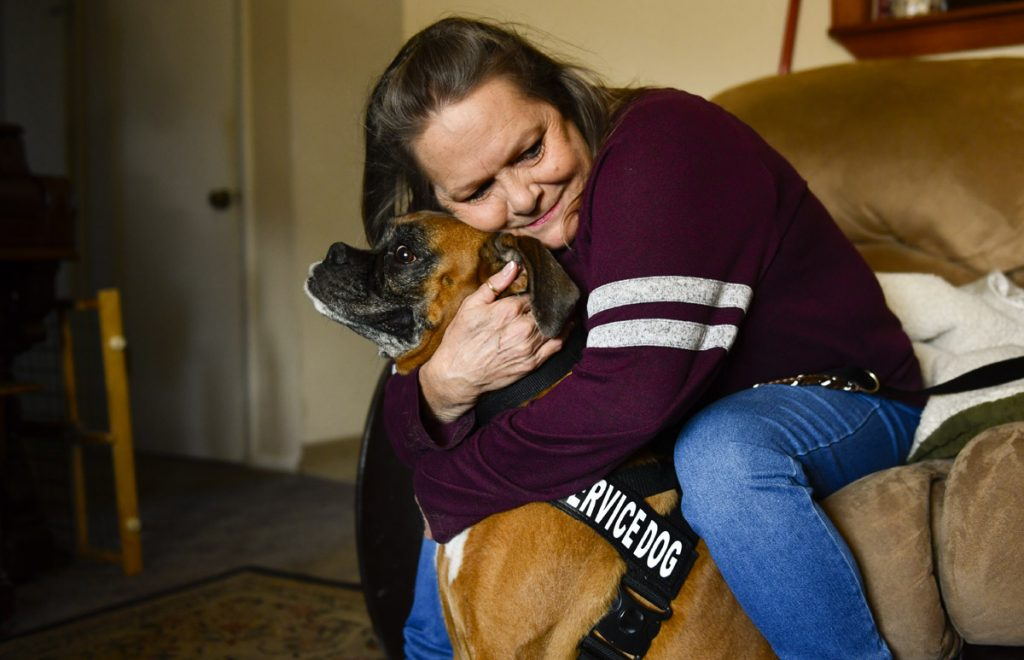 A woman hugs her boxer dog. The dog wears a black service harness because it used to be the woman's service dog when she was blind.