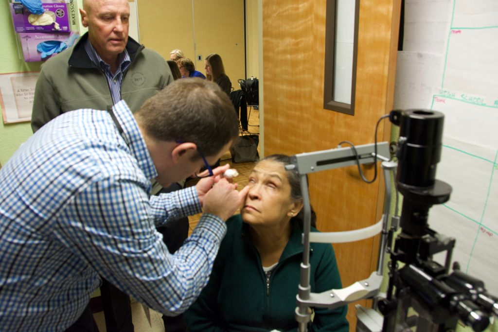 Eye doctor Frank Siringo exames an uninsured patient in a makeshift office at the DAWN Clinic in Aurora.