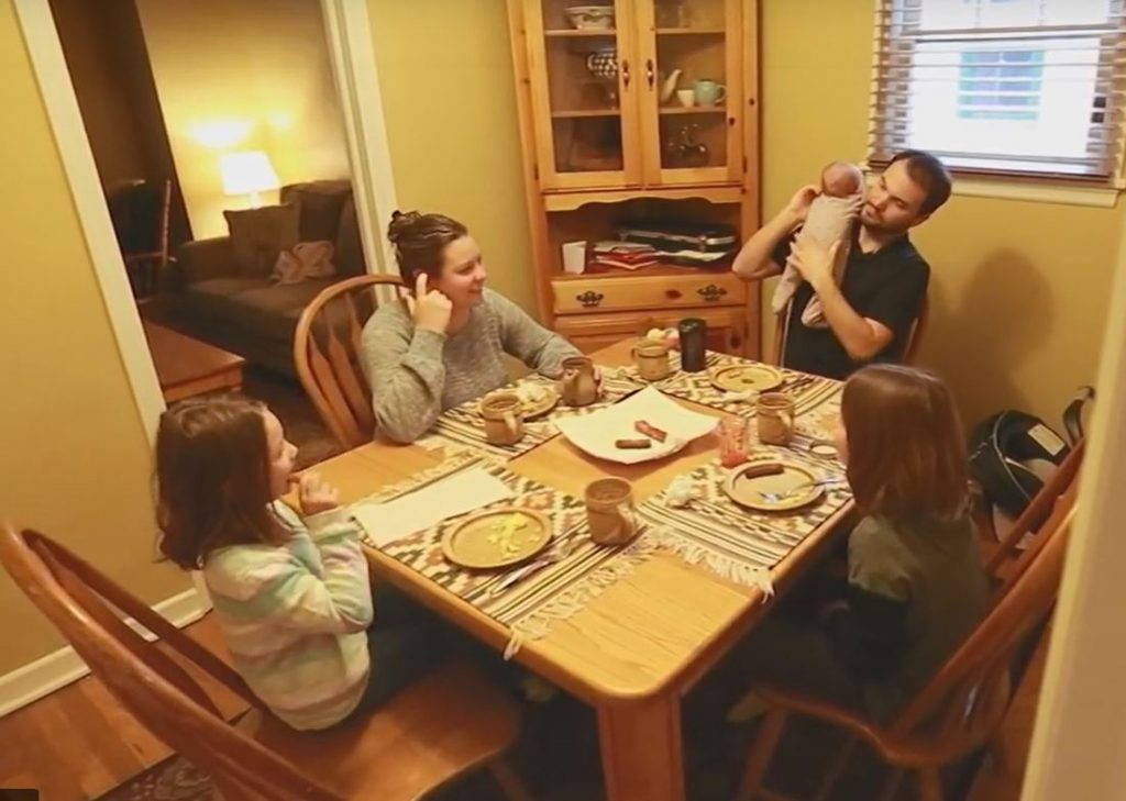 Makai Hall sits down to breakfast with his wife and three daughters.