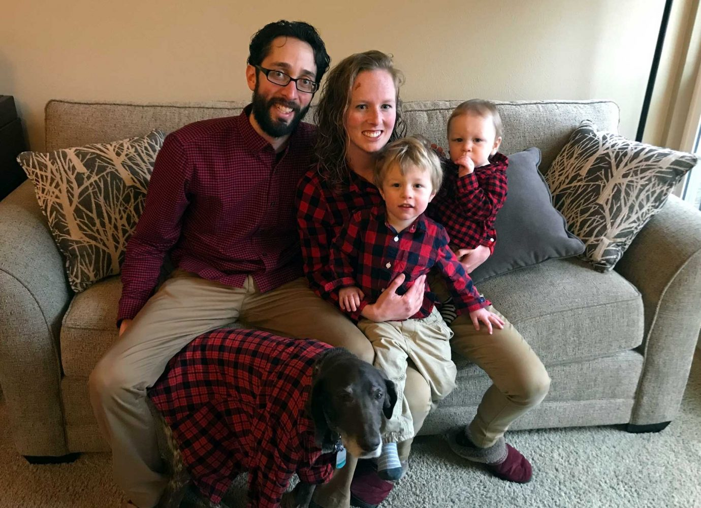 dad, mom, two young kids and a dog sitting on the couch wearing red flannel.
