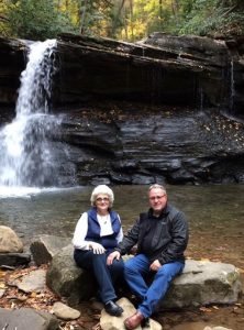 An older couple poses with a small waterfall behind them.