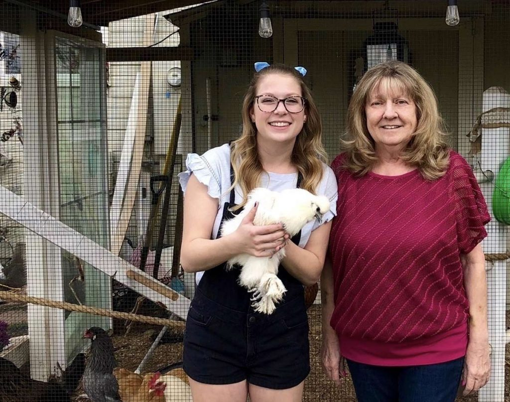 A daughter holds a chicken as she stands next to her mom outside their chicken roost.