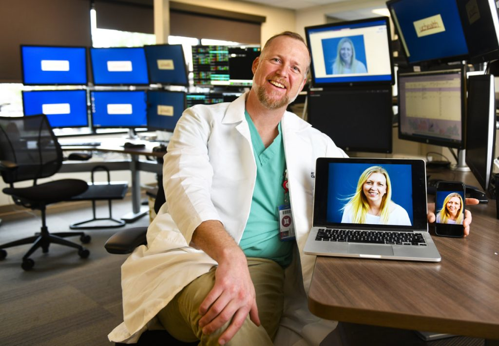 Portrait of Dr. Chris Davis with computer screens and a portrait of a patient during a Virtual Urgent Care visit.