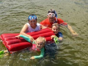 A photo of Lydia Friese in the water with her husband and grandchildren