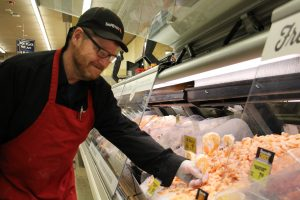 Carey Robinson adjusts a price sign at the seafood counter in the grocery store where he works.