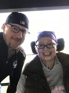 Jamie and Troy Ketchum pose at a Colorado Rockies game. She is in a wheel chair after surviving terrible burns. But she continues to smile.