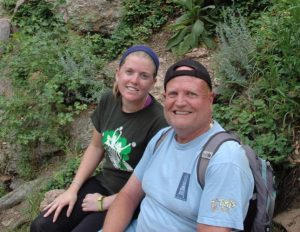Image of Amy sitting next to her father during a break on a hike.