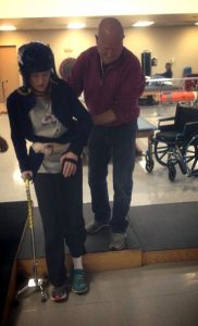 image of amy, which a helmet and a cane, being helped to walk by her father while in rehab.