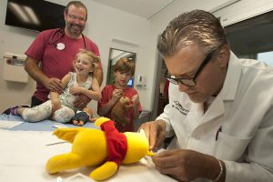 Doctor sews up a stuffed bear while two kids watch in an emergency room.