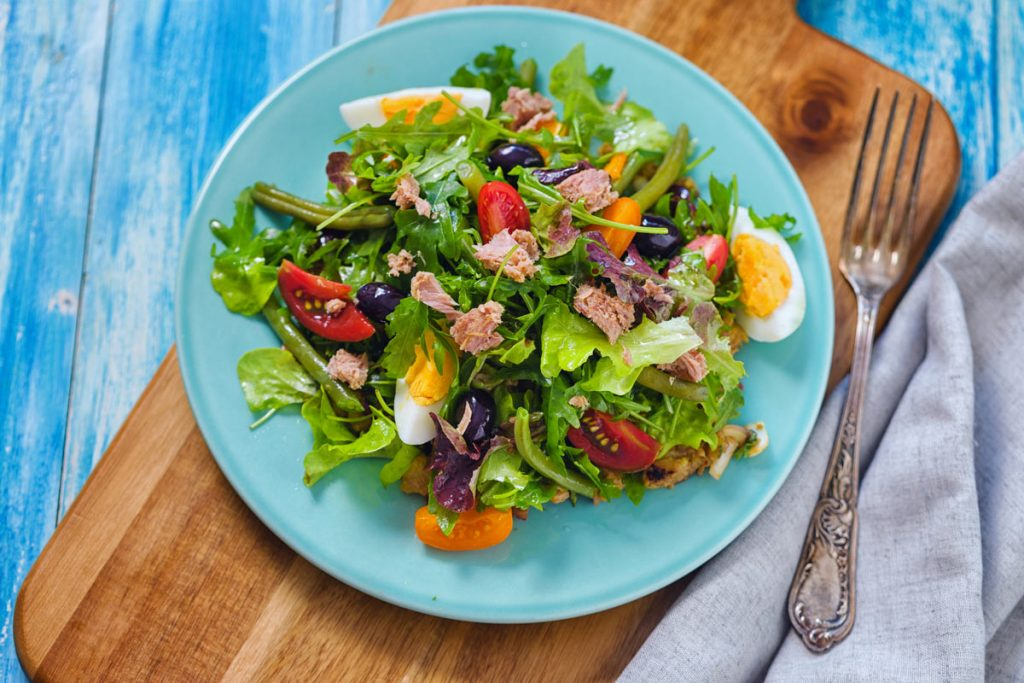 salad nicoise on a blue plate