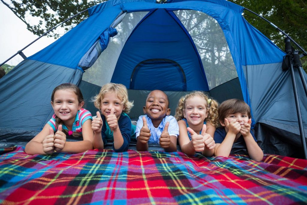 Children lay on their bellies in front of a tent. having a fun place for them to play should be part of your kid camping kit.