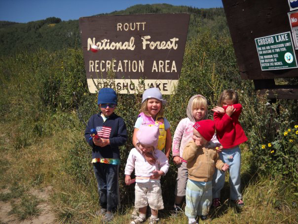 Kid campers pose in front of a Forest Service sign near Steamboat, there parents whom created a kid camping kit to help them enjoy their trips.
