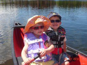 Two little boys rowing a canoe on a lake.