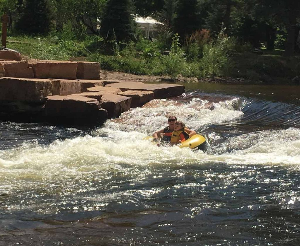 woman and child going down a rapid in Colorado summer tubing river.
