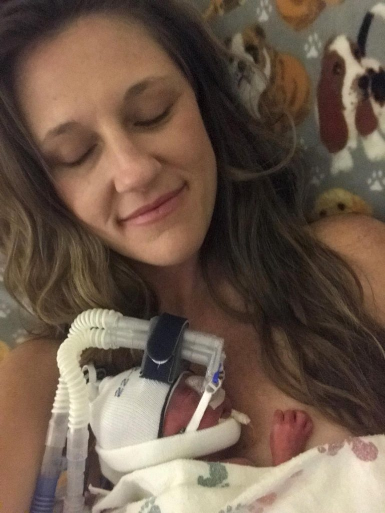 A preemie baby nestles into his Mom's chest.