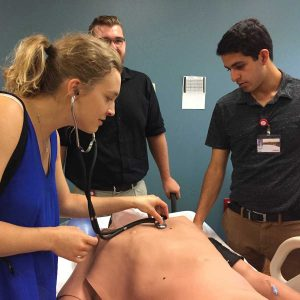 student listens to heartbeat on a simulation dummy