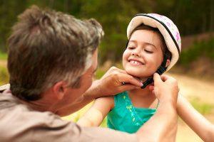 man buckling child's bike helmet