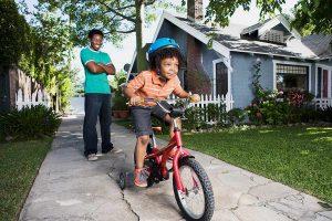 dad teaching kid how to ride a bike